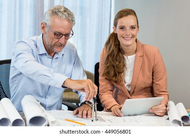 Businesswoman holding digital tablet while coworker working on blueprint with compass in the office