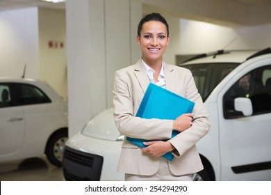 Businesswoman holding document while looking at camera at new car showroom