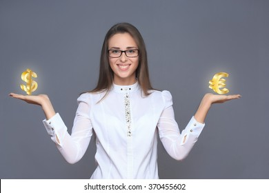 businesswoman holding euro and dollar symbols or signs.