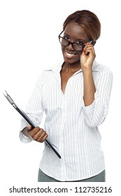 Businesswoman holding file and adjusting her spectacles. All on white background