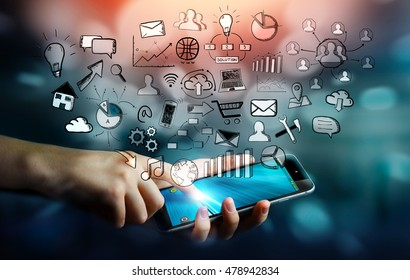 Businesswoman holding hand drawn web icons over her mobile phone