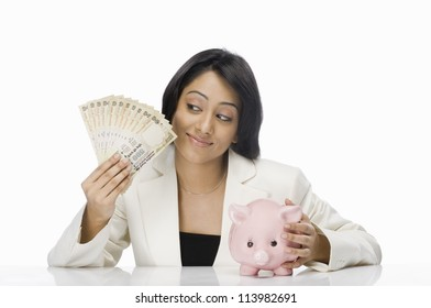 Businesswoman holding Indian paper currency and piggy bank
