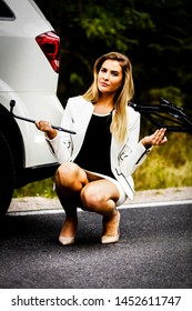 Businesswoman holding jack in hand and don't know how to use it for changing wheel.