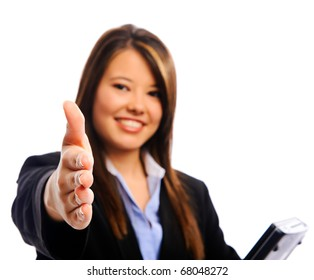 Businesswoman holding a laptop offering a handshake, selective focus on hand