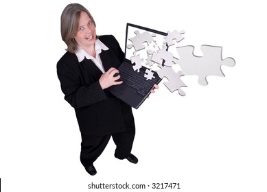 Businesswoman holding a laptop with puzzle pieces flying out with a funny expression isolated over white