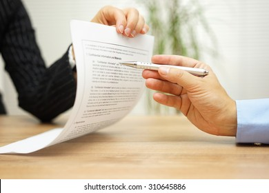 businesswoman holding legal document and  wants an explanation about article in contract