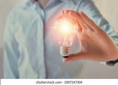 businesswoman holding light bulb, innovation and inspiration concept