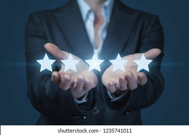 A businesswoman is holding a line of golden shining stars at the dark background. The concept of successful rating.
