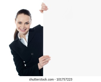 Businesswoman holding a long blank banner ad isolated over white background