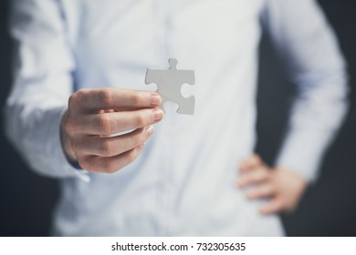 Businesswoman holding a missing piece of a jigsaw puzzle. Shallow focus.