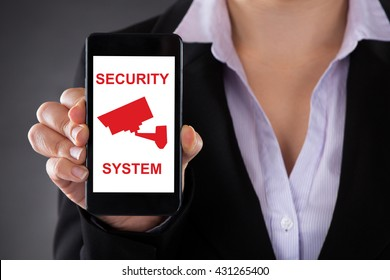 Businesswoman Holding Mobile Phone With Security System Icon On It