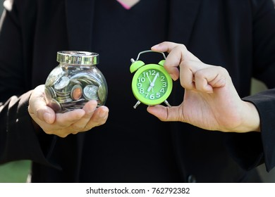 businesswoman holding money with time clock, idea for saving money and race against time