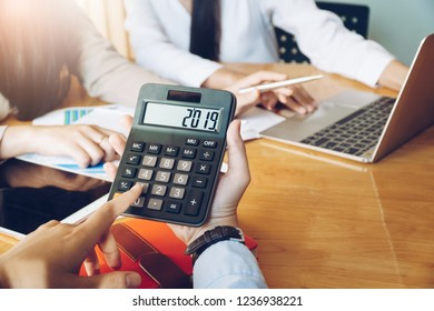 Businesswoman holding number 2019 on calculator in meeting room. Business meeting time.