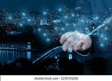 A businesswoman is holding a padlock on her arm surrounded by digital wireless connections at the night city background. The concept is the security system work principle