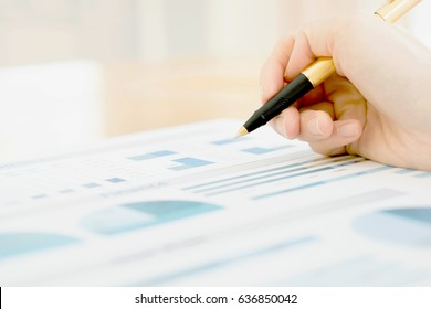 Businesswoman holding a pen and analyze data
