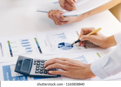 Businesswoman holding a pen pointing the graph  with partnership to analyze the marketing plan with calculator. Meeting brainstorming and discussing project. Teamwork concept.