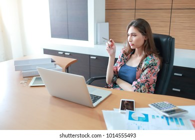 businesswoman holding pen and thinking of something