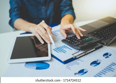 Businesswoman holding a pen and using  calculator to calculate and analyze business cost data such as pie charts and bar charts on the desk in the workplace.