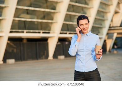 Businesswoman holding phone and cup. Young caucasian female. Telephone etiquette tips.