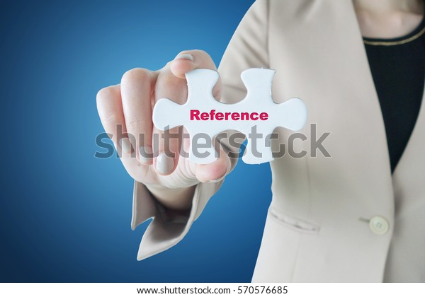 Businesswoman holding a piece of jigsaw puzzle: Reference