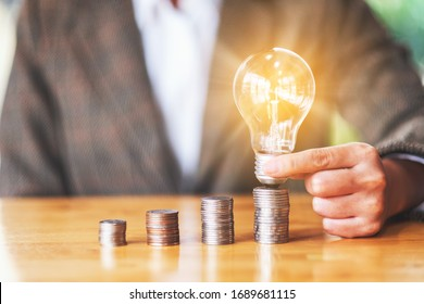 Businesswoman holding and putting light bulb on coins stack on table for saving energy and money concept