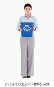 Businesswoman holding a recycling bin against a white background