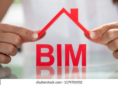 Businesswoman Holding Roof Over BIM Text On Reflective Desk