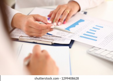 Businesswoman holding a silvery pen in her hand indicates the interlocutor for a digram on the form of annual report on the financing of organizations trains the processing of this statistical study