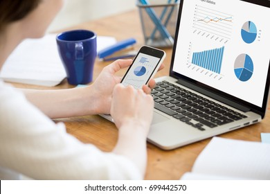 Businesswoman holding smartphone while working with laptop at home office desk, using cross platform responsive design apps for project analysis, analyzing cloud data statistics, close up rear view