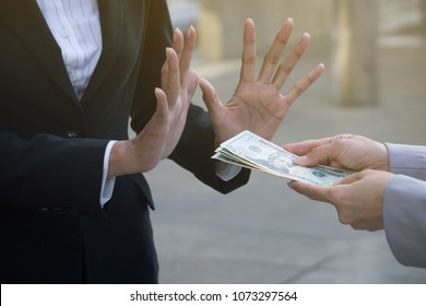businesswoman holding stack of money in hand offering bribe, hand gesture rejecting the proposal.