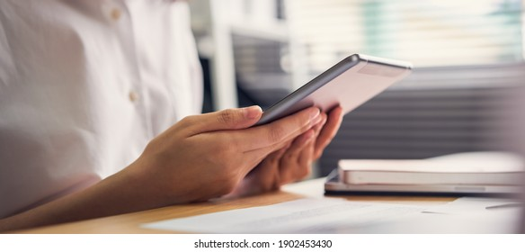 Businesswoman holding tablet and used to work online on the table at office.