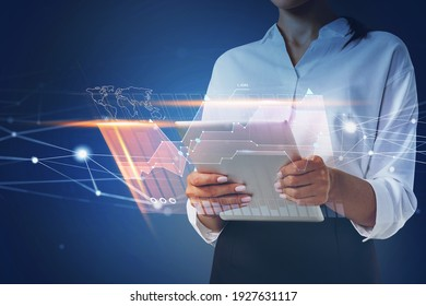 Businesswoman holding tablet and using technological approach to optimize business process. System hologram charts and graph flying nearby smartphone. Office on background.