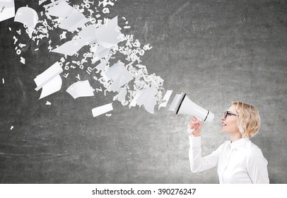 Businesswoman holding white loudspeaker, many letters and paper flying from it. Black background. Concept of informing.