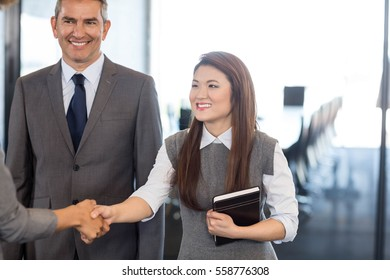 Businesswoman interacting and shaking hands with team in office