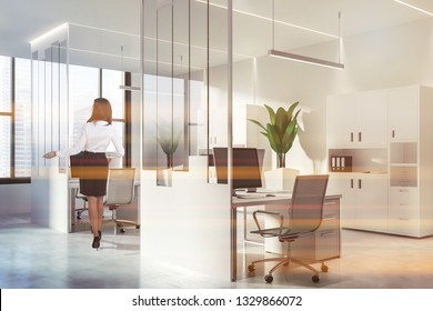 Businesswoman in interior of modern office with white and glass walls, concrete floor, large windows, white computer tables with metal chairs and bookcases with folders. Toned image