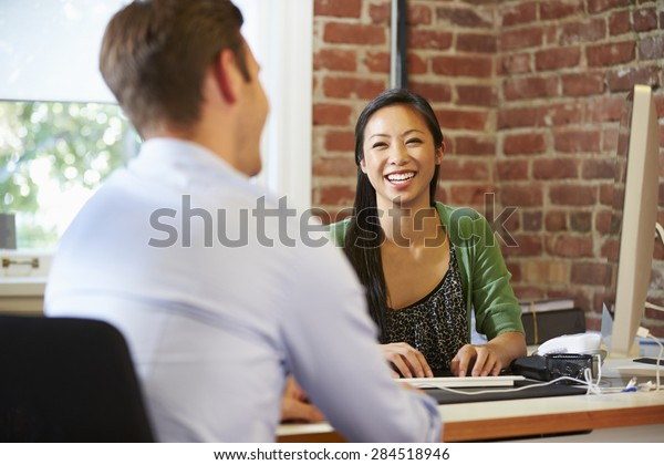 Businesswoman Interviewing Male Job Applicant In Office