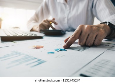 Businesswoman investment consultant analyzing company annual financial report balance sheet statement working with calculator and financial documents. Concept picture of business, market, office, tax.