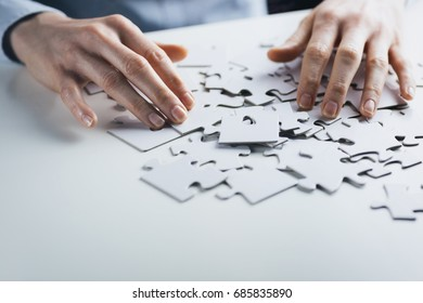 Businesswoman with a jigsaw puzzle on a white table.