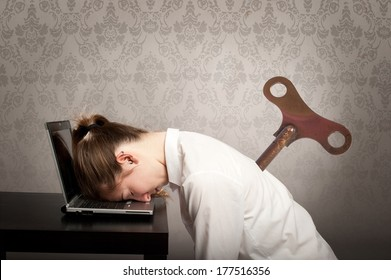 businesswoman with a key winder on her back sleeping on laptop