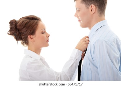 Businesswoman knotting the necktie of the businessman, helping and assisting him getting dressed. Isolated over white.