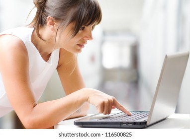 businesswoman at laptop against interiors background
