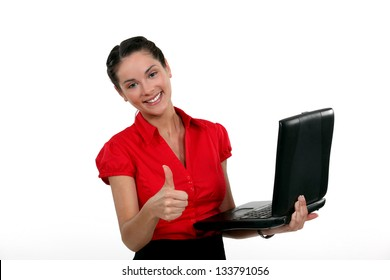 A businesswoman with a laptop giving the thumb up.