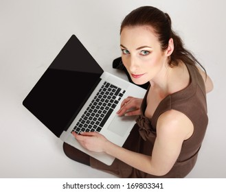 Businesswoman with laptop sitting on the floor isolated on white background