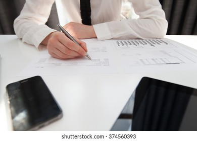 businesswoman with laptop writes on a document at her office