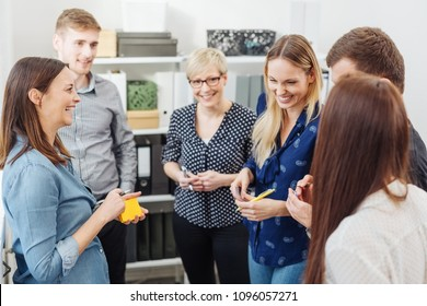 Businesswoman laughing at a young female colleague in a meeting with a diverse group of business people gather together in an office