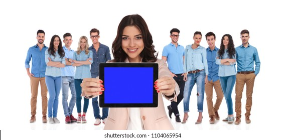 businesswoman leader of casual group showing blank screen of tablet while standing on white background in front of them