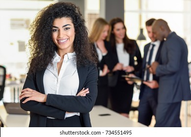 Businesswoman leader looking at camera in modern office with businesspeople working at the background. Teamwork concept. Muslim woman.