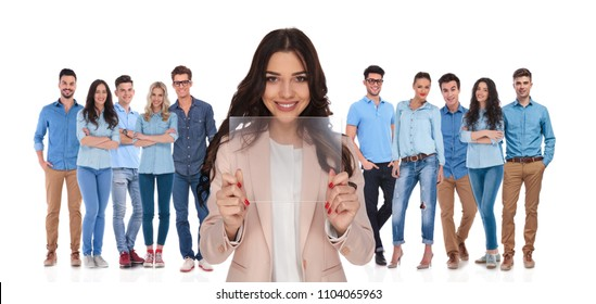 businesswoman leader showing futuristic transparent gadget in front of her casual group while standing on white background
