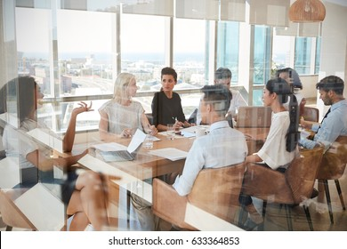 Businesswoman Leads Meeting Around Table Shot Through Door