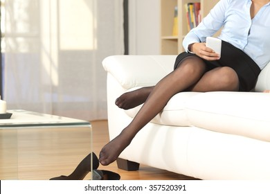 Businesswoman legs with nylons resting after work texting on a mobile phone